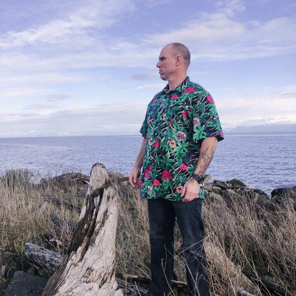 man in hawaiian shirt on rocks by ocean